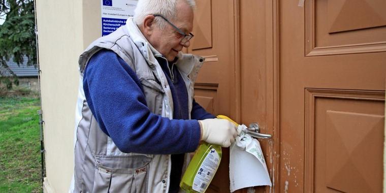 Kirchenwart Hartmut Müller reinigt die Klinke, an der sich ebenfalls Kotspuren befanden. Quelle: Andreas Kaatz